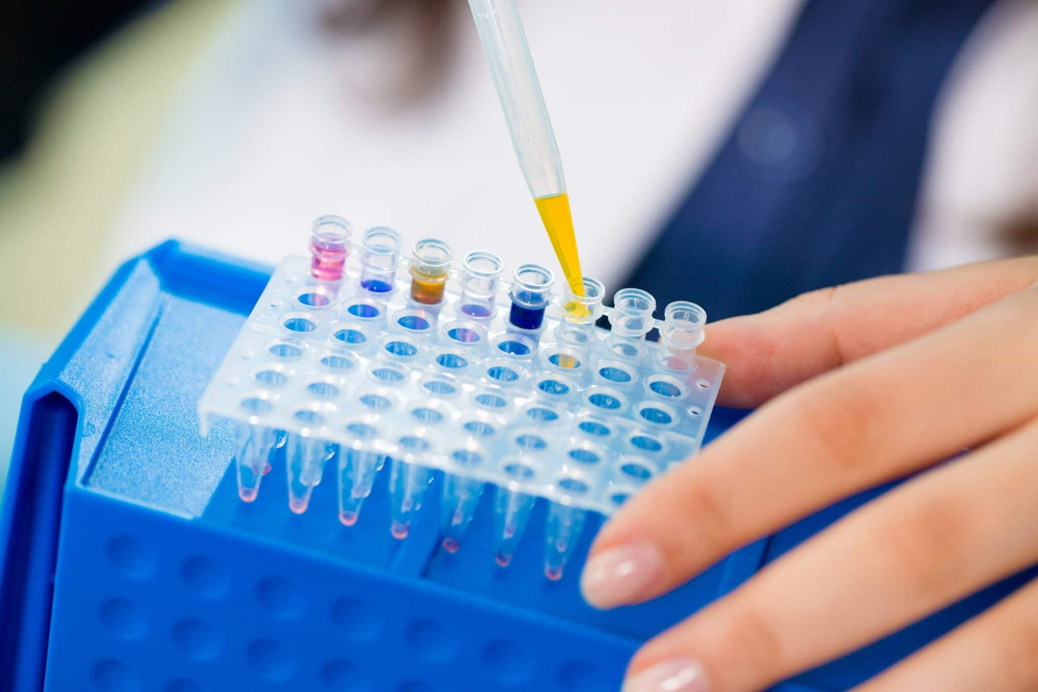 Young female technician in genetic laboratory with PCR